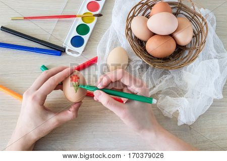 woman's hand paints hen's egg food marker for Easter