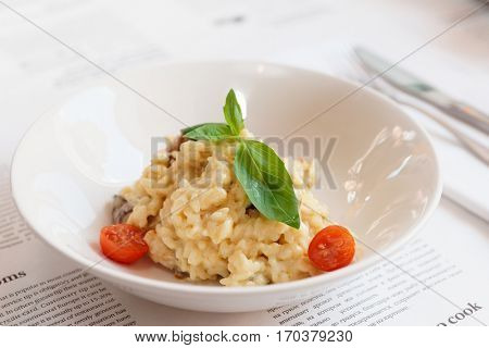 Creamy risotto in porcelain plate served in deep porcelain plate