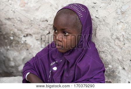 Zanzibar, Tanzania - July 14, 2016: Small muslim girl in a hijab sitting near a wall of a shack in Tanzania