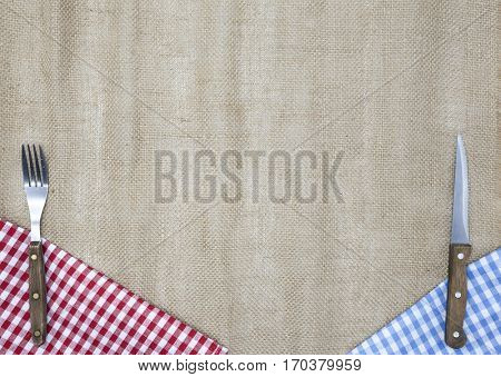 Light fabric along the edges of the table, fork and knife. Background to create a menu of the tavern.Background to create the restaurant's menu. Linen tablecloth fork knife on a bright checkered cloth