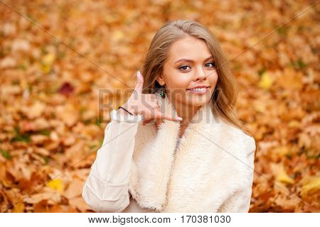 Call Me. Young beautiful blonde woman in autumn park