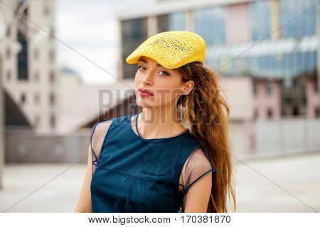 Street Fashion. Portrait of a brunete woman in yellow hat and blue dress