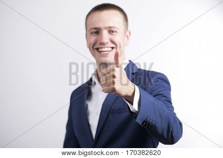Gestures of hands: focus on the arm. Young Happy Business Man in studio