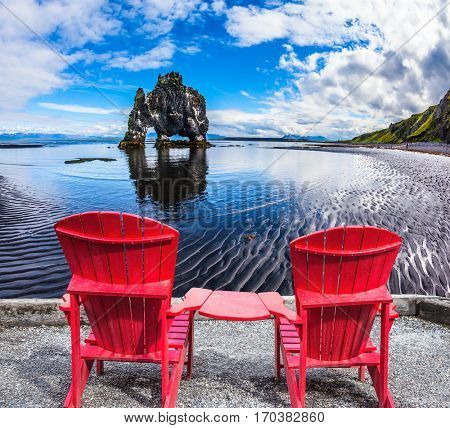 Pair of comfortable red deck chairs set in front of Magic Rock Hvitsercur. Northern coast of Iceland. Concept of extreme northern tourism