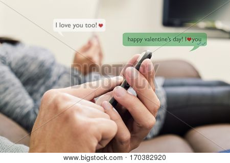 a young caucasian man and a young caucasian woman sending and receiving text messages in their smartphones with the text Happy valentines day, I love you and I love you too