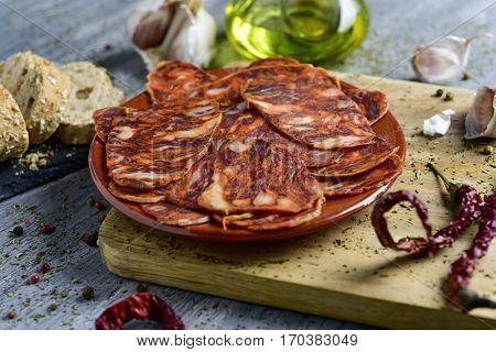 closeup of an earthenware plate with some slices of spanish chorizo, cured pork sausage, some slices of bread, a glass cruet with olive oil and some garlics, on a rustic gray wooden table