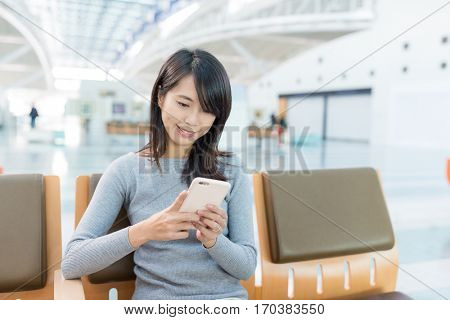 Young Woman texting on cellphone at airport