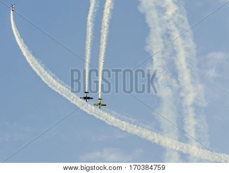 Aerobatic Pilots With Her Colored Airplanes Training In The Blue Sky, Trace Colored Smoke