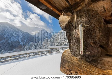 Outdoor Thermometer showing minus - 10 degrees celsius outside mountain hut with mountain view and blue sky during cold winter in Austria, Europe