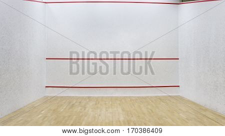 Empty squash court with a wooden floor. Wall with red lines in squash hall