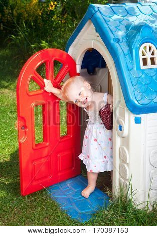 Little baby girl wearing white dress looking out from plastic play house doorway in a summer playground