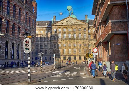 AMSTERDAM, NETHERLANDS - MAY 3, 2016: City street view with the Magna Plaza and the Royal Palace and people near Dam square, Amsterdam, the Netherlands