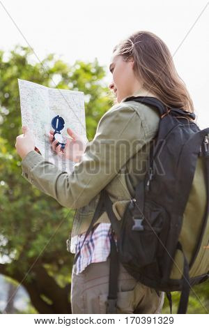 Woman using map and compass in the countryside