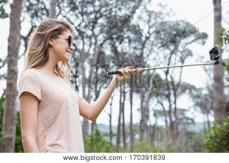 Smiling woman taking selfies in the countryside