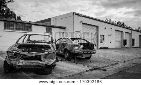 Abandoned wrecked cars on drive way in front of buildings black and white