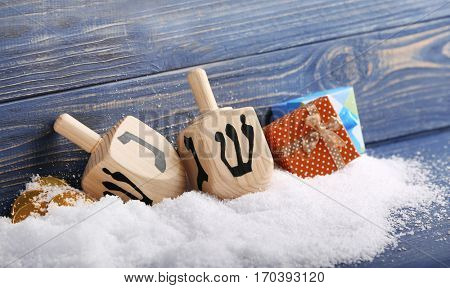 Composition of dreidels for Hanukkah and snow on wooden background