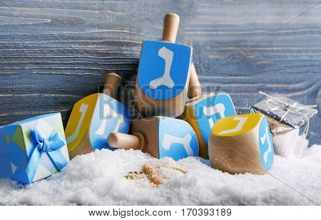 Composition of dreidels for Hanukkah and snow on wooden background, close up