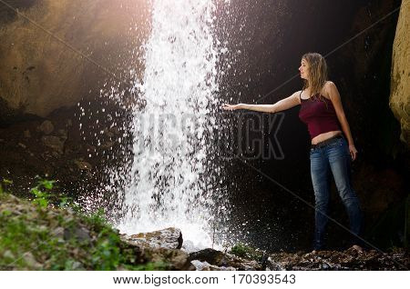 Young sexy wet girl is enjoying the rest near the waterfall in Tien-Shan mountains