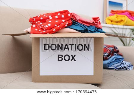 Donation box with clothing on sofa
