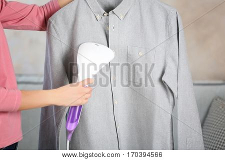 Woman ironing shirt with garment steamer