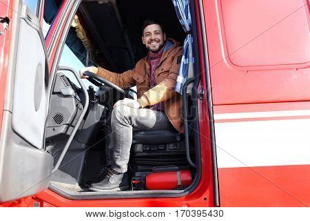 Driver in cabin of big modern truck