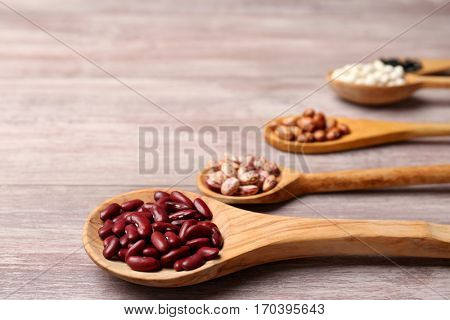 Assortment of haricot beans in spoons on wooden background