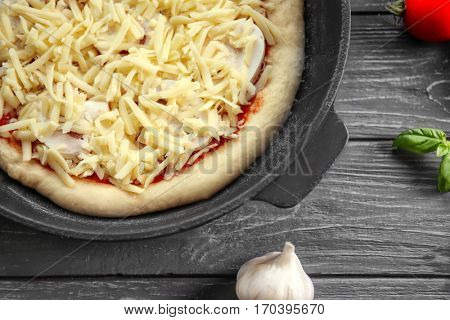 Unbaked pizza in pan on wooden table