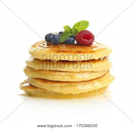 Delicious pancakes with berries and sweet syrup on white background