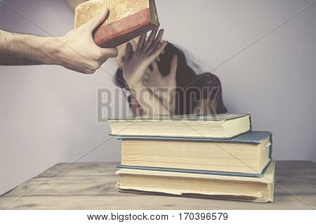 Man about to beat his wife with book