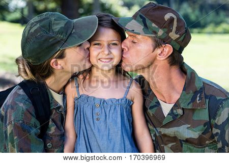 Soldier couple reunited with their daughter in the park on a sunny day