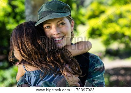 Happy soldier reunited with her daughter in the park on a sunny day