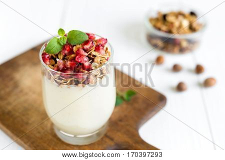Healthy breakfast concept. Vanilla cream with fresh granola in a glass topped with pomegranate and mint arranged on white wooden table.