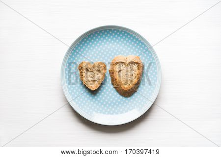 Top view of natural heart-shaped sliced bread on blue plate with white background. Love concept.