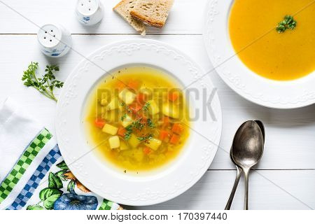 Two plates of vegetable soup and cream with bread fresh parsley spoons salt and pepper shakers on white wooden table
