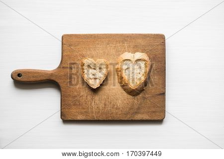 Top view of two pieces of fresh sliced bread in a heart-shaped natural form on cutting board with white background. Love concept.