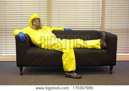 boredom - professional in protective clothing, mask and gloves, lying and relaxing on the couch in office