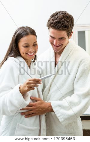 Happy couple in bathrobe looking at pregnancy test in bathroom