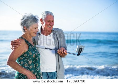 Senior couple taking a selfie at the beach
