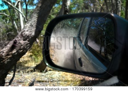 Reflections in a side view mirror of a car driving in the bush. Rear view car mirror in forest live green. Dirt road leading up to a slavery plantation. Concept of 4wd off-road driving in the nature.