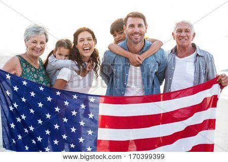 Happy family with an american flag at the beach