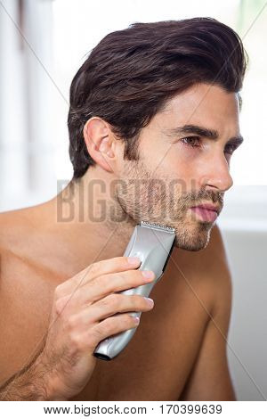 Close-up of young man shaving with trimmer in bathroom