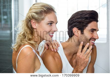 Young woman standing beside man and checking stubble in bathroom