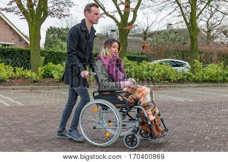 Man pushing a woman in a wheelchair at a parking place in a Dutch village