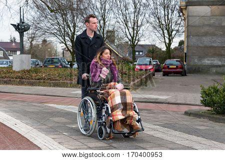 Man pushing a woman in a wheelchair at a zebra crosssing in a Dutch village