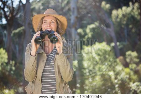 Smiling woman using binoculars in the forest