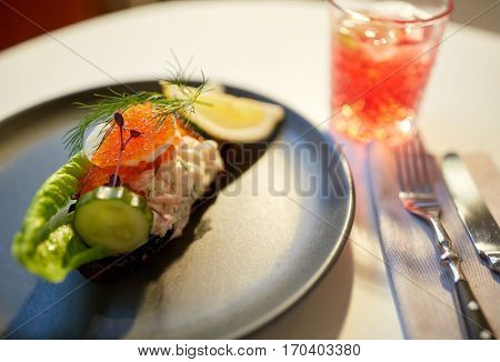 food, new nordic cuisine, culinary and cooking concept - close up of toast skagen with shrimps, fish roe and buttery bread on plate at restaurant