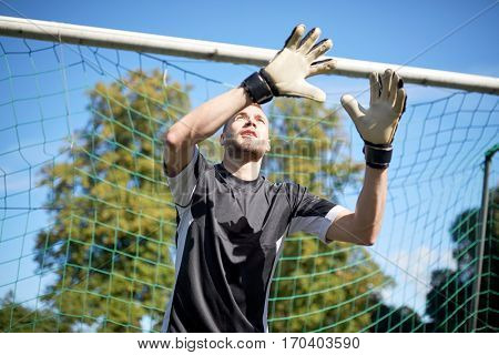 sport and people - soccer player or goalkeeper at football goal on field