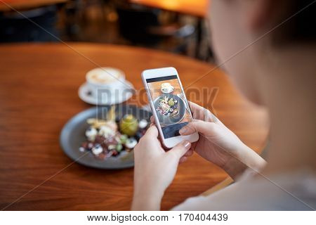 food, new nordic cuisine, technology and people concept - woman with smartphone photographing chocolate ice cream dessert with blueberry kissel, honey baked fig and greek yoghurt at cafe