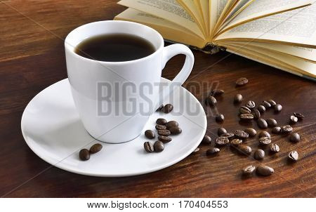 Breakfast scene with coffee cup, open book and coffee beans on a wooden table. Morning scene with hot coffee.