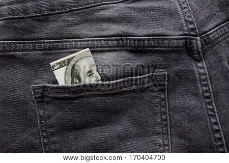 finance, clothes and currency concept - dollar money in back pocket of denims or jeans